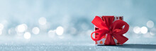 Beautiful Red Christmas Gift With Large Bow On Shiny Blue Background And Defocused Christmas Lights In The Background. Christmas Banner With Copy Space.