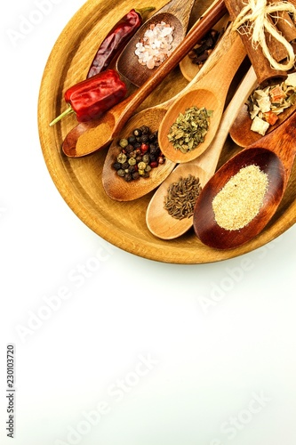 Keuken foto achterwand Kruiderij Different spice types on a wooden spoon. Sale of spices. Spices on a white background.