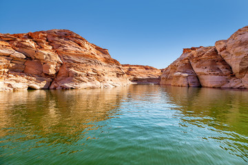 Fototapeta na wymiar Glen Canyon coloured sandstone cliffs filled with water, near Lake Powell and the Colorado River, straddling the border between Utah and Arizona. National park and popular tourist attraction