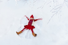Child Making Snow Angel. Kids Winter Outdoor Fun.