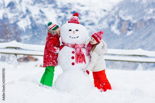 Fototapeta Child building snowman. Kids build snow man.