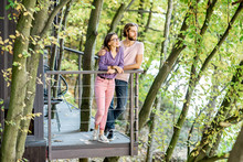 Portrait Of A Beautiful Couple Standing Together On The Balcony In The Forest Enjoying The Nature