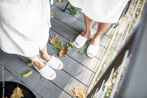 Couple in bath robe and slipppers standing on the terrace with beautiful leaves outdoors Wallpaper Mural