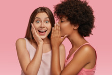 Young Black Woman Whispers Secret To Her Caucasian Friend, Gossip Together And Spread Rumours. Emotional European Girl Feels Amazed To Hear Confidential Information From Companion. Secrecy, Gossiping