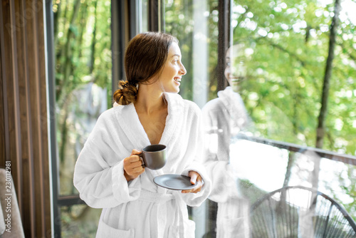 Fotografie, Obraz  Woman in bathrobe standing near the window with beautiful view on the forest in