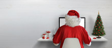 Santa Claus Working On A Computer In His Office During Christmas Holidays. Empty Space On Wall For Text.