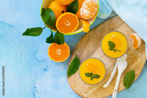 Deurstickers Buffet, Bar Panna cotta with tangerines jelly and mint, Italian dessert, homemade cuisine. Top view flat lay background. Copy space.