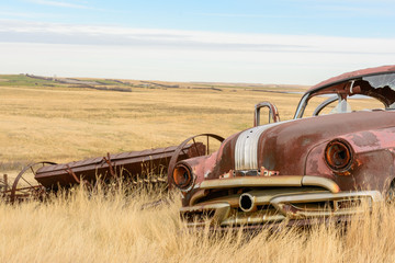 abandoned old car and seeding equipment