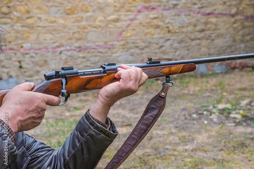 Men pulling the trigger of hunting carbine