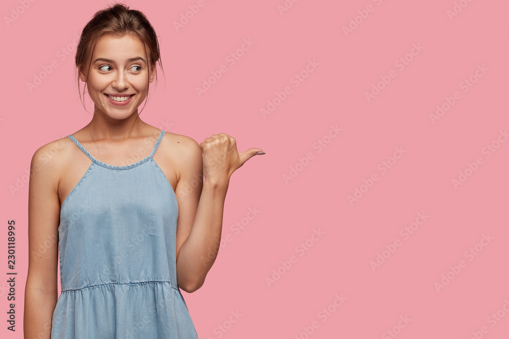 Fototapeta Studio shot of pleased European woman with joyful expression, enjoys watching cool performance, dressed in fashionable dress, isolated over pink background. Advertisement and promotion concept