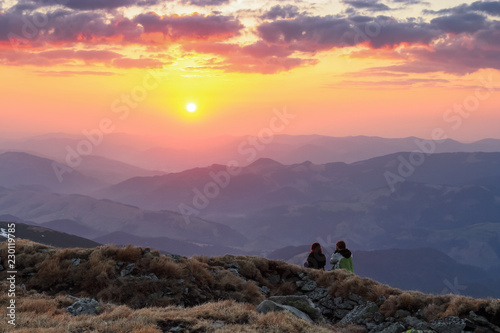 A couple in love is sitting on the rocks and watching the scenery of the sunset, high mountains, sky with clouds. The horizon lights up with orange and red colors.