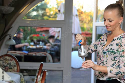 Plakat Piękna dziewczyna, kelnerka zapala świecę w restauracji.