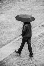 Portrait Of Man Walking With Umbrella On Cobbles Place