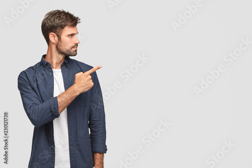 Fototapeta Stylish unshaven young man with dark bristle, attracts your attention to something, points with index finger at blank space, shows free space for your advertising content, stands sideways indoor obraz