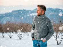 Handsome Young Man Outdoor In Winter Fashion, Wearing Black Coat And Woolen Scarf In Snow Environment