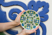 In The Hands Of A Decorative Plate On A Background Of Blue-green Wall, Decorative Plate With Blue, Green Flowers, Painted Plates,