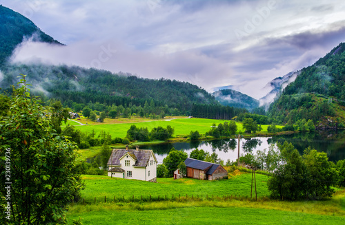Typical countryside Norwegian landscape with houses on the shore of the lake. Cloudy summer morning in Norway, Europe. Artistic picture. Beauty world.