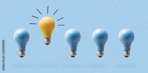One outstanding idea concept with light bulbs on a blue background Canvas Print