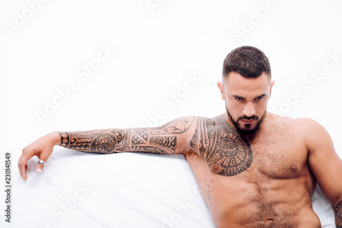 Stampa su Tela Nude male model lies in white bed