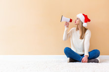 Young Woman With Santa Hat Holding A Megaphone On A White Carpet