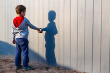 Boy And His Shadow. Lonely Little Child Playing With His Shadow Outside. Imaginary Friend. The Concept Of Autism And Loneliness. Copy Space For Your Text
