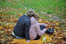 Mother And Daughter, Both Blond Hair, Sit On Yellow Blanket In Park, Autumn / Fall, Colorful Leaves On Ground, Few Pumpkins Next To People, They Are Close To Each Other, With Good Feelings.