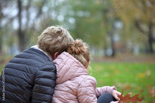 Mama z córką, obie blondynki, siedzą, tyłem, przytulone, w parku, dziewczynka trzyma w ręku jesienny liść, w tle rozmyta jesienna przyroda Wallpaper Mural