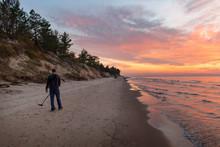 Treasure Hunter With Metal Detector On Sunset Beach