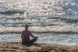 Woman Meditating on a Southern Italian Beach in the Sun