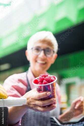Fotografía  Senior woman sells raspberries on market