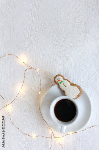 Fototapeta Happy Christmas drink/ small cup of black coffee with ginger cookies in the shape jolly snowman with festive garland on the table top view obraz na płótnie
