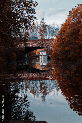 Tuinposter Baksteen Concrete arch bridge on a river with autumn tree color tones and sunset sunlight. Südsee in Braunschweig, Germany