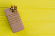 canvas print picture - Gift box wrapped in cardboard paper. Copyspace. Yellow wood background.