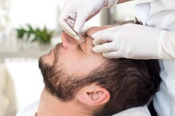 Kosmetyczka podczas zabiegu regulacji brwi u mężczyzny. Wyrywanie zbędnych włosów na brwiach