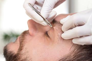 Kosmetyczka depiluje zbędne włosy na brwiach mężczyzny.