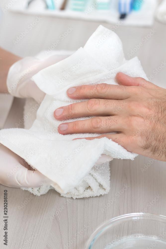 Fototapeta Męskie dłonie wycierane ręcznikiem przez dłonie kosmetyczki podczas zabiegu kosmetycznego manicure. Mężczyzna w salonie kosmetycznym.