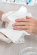 Męskie dłonie wycierane ręcznikiem przez dłonie kosmetyczki podczas zabiegu kosmetycznego manicure. Mężczyzna w salonie kosmetycznym.