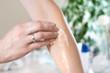 Zabieg kosmetyczny. Kobieca dłoń nakłada balsam na przedramię.