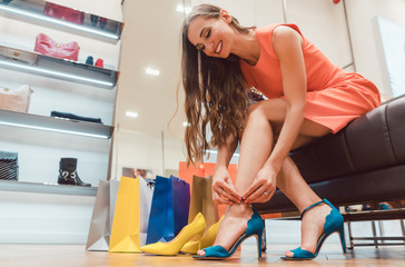 Fototapeta Woman trying to fit new shoes she wants to buy in store