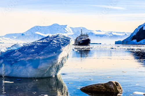 Poster Antarctica Touristic antarctic cruise ship among the icebergs with glacier in background, Neco bay, Antarctica