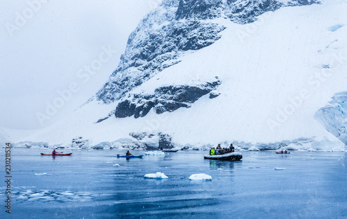 In de dag Antarctica Snowfall over the motor boat with tourists and kayaks in the bay with rock and glacier in the background, near Almirante Brown, Antarctic peninsula