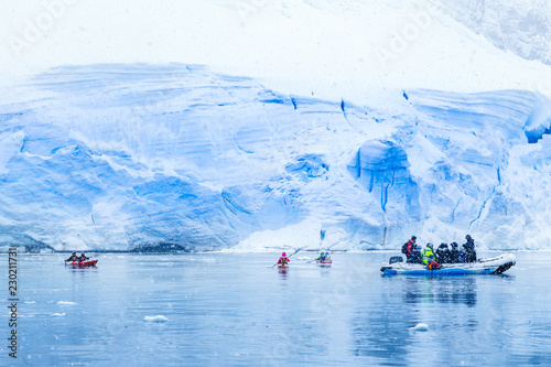 Photo Stands Antarctic Snowfall over the motor boat with tourists and kayaks in the bay with huge blue glacier wall in the background, near Almirante Brown, Antarctic peninsula