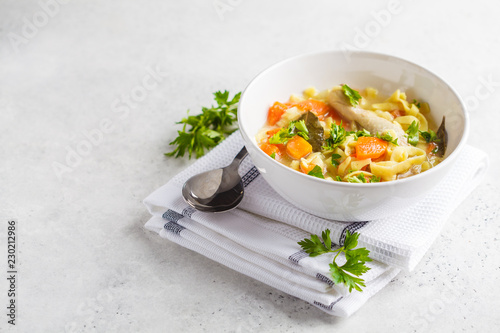 Chicken noodle soup and vegetables in a white bowl on a white background, copy space.