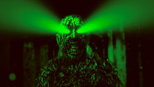 Dark Zombie With Green Rays From The Eyes In Dungeon. Green Color