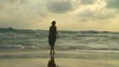 Lonely girl walks along beach and looks at horizon.