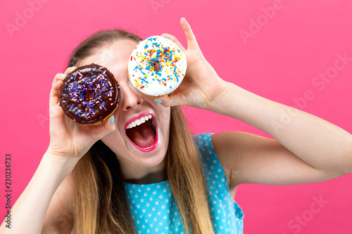 Young woman with donuts on a pink background