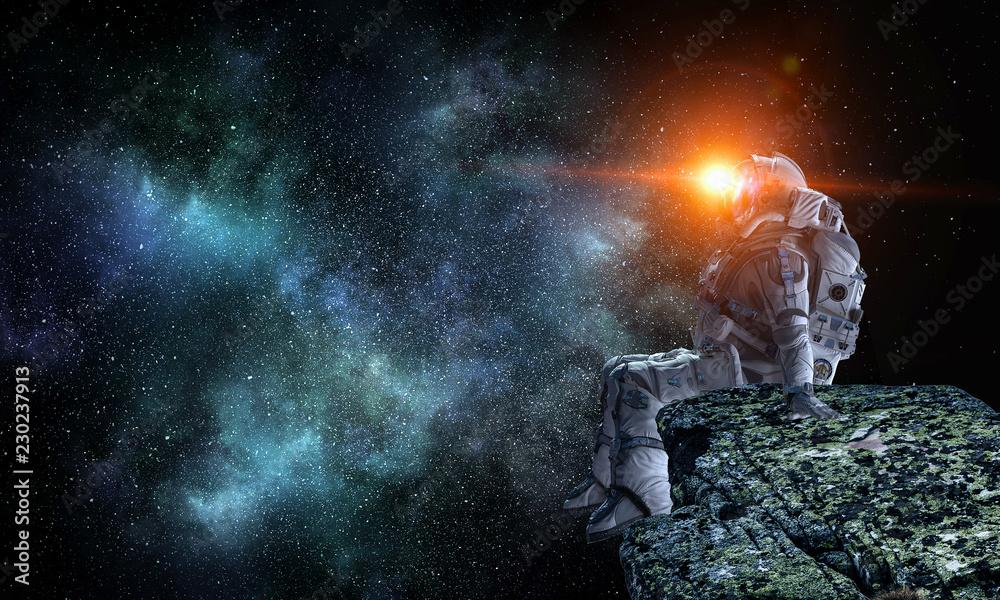 Fototapeta Spaceman on rock edge. Mixed media