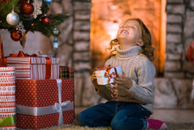 Little Girl Child At Home By The Fireplace And Christmas Tree With Gifts And Luminous Garlands Celebrates Christmas
