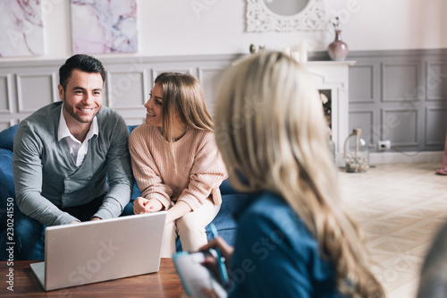 Fotografie, Obraz Happy young loving couple sitting together with their financial advisor
