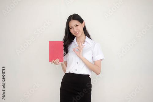 Fotografía  Portrait of thai adult student university uniform beautiful girl read red book